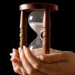 Hourglass in hands on a black background — Stock Photo