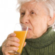 The elderly woman with a juice glass — Stock Photo #5335650