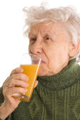 The elderly woman with a juice glass — Foto de Stock
