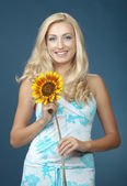 The beautiful girl with a sunflower — Stock Photo