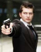 Businessman with gun — Stock Photo