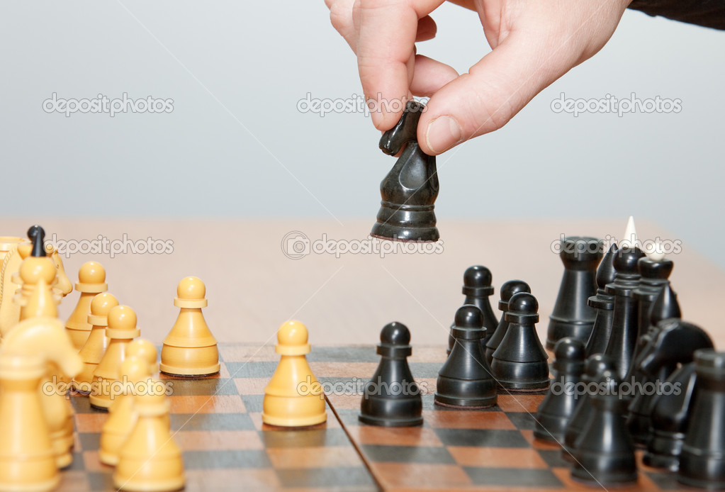 The hand moves a horse in chess game — Stock Photo #5324408