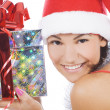 Santa woman showing gift wearing Santa hat. - Stock Photo