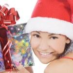 Santa woman showing gift wearing Santa hat. — Stock Photo #4247488