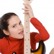 Sexy young female posing with guitar over white — Stock Photo