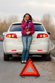 Woman calls to a service standing by a white car — Stock Photo