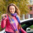 The happy woman showing the key of her new car — 图库照片