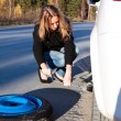 Young woman and the car with deflated wheel — 图库照片