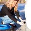 Young woman and the car with deflated wheel — Stock Photo #4000335