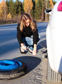 Young woman and the car with deflated wheel — Stock Photo