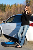 Young woman standing by her damaged car — Stock Photo