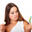 Confused girl looking at condom and contraceptive pills — Stock Photo