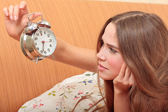 Young girl and alarm clock. Bedtime scene — Stock Photo
