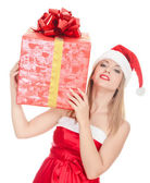 Cheerful santa helper girl with big gift box on her shoulder — Stock Photo
