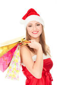 Pretty girl in a red Christmas hat with colorful bags — Stock Photo