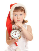 Little girl wearing red Santa's hat with a big alarm clock — Stock Photo