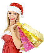 Hübsches Mädchen in eine rote weihnachtsmütze mit bunten Taschen — Stockfoto