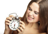 Scared girl holding an alarm clock in the hands — Stockfoto