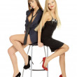 Beauty girls sit on bar stool — Stock Photo