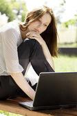 Jovem mulher com um laptop no parque — Fotografia Stock