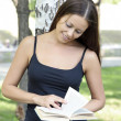 Young pretty woman reading a book at park — Stock fotografie