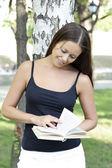 Młoda ładna kobieta, czytając książkę w parku — Zdjęcie stockowe