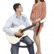 Pregnant woman and a man playing guitar for her - Stock Photo