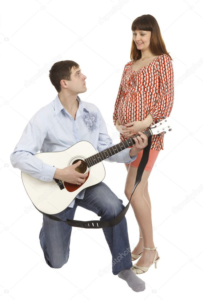 Pregnant woman and a man playing guitar for her, isolated on white background.  Stock Photo #4785959