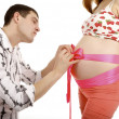 Man making a bow on a belly of pregnant woman — Stock Photo
