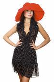 Mooie jonge vrouw in zwarte jurk en rode hoed — Stockfoto