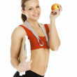 Sports woman holding an apple and carrying a weight scale — Stock Photo