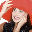 Royalty-Free Stock Photo: Pretty excited woman in red hat posing against white background.