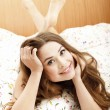 Smiling woman in a bed — Stock Photo