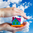 Toy house in human hands - Against the sky - Stock Photo