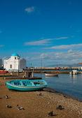 Písečná pláž s rybářskými čluny a slavný kostel — Stock fotografie