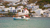 Fishing boat in the harbor of Mykonos against the white buildings of the is — Stock Photo