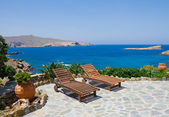 Garden with sun loungers on the background of the sea. Mykonos. Greece. — Stock Photo