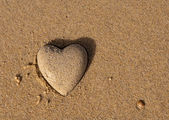 Heart shape of the sand near the sea - a symbol of love — Stock Photo