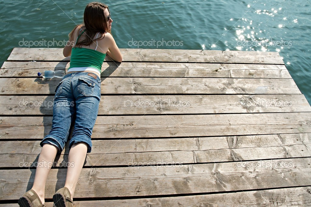 Girl relaxing on a pier at a lake in summer  Stock Photo #4931833