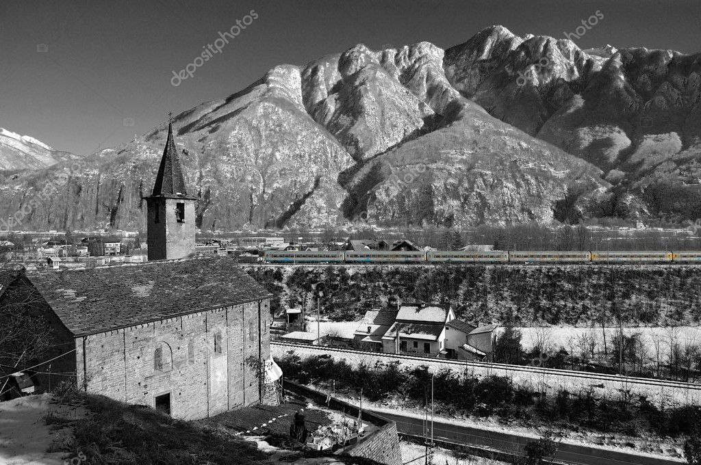 Black and white view on Alpine S.Quirico Church in winter, Ossola valley and mountains in background, Domodossola, Italy — Stock Photo #4386995