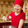 Stock Photo: Boy helping at kitchen with baking a pie, little chef