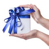 Mani tenendo il regalo in pacchetto con nastro blu isolato su bianco — Foto Stock