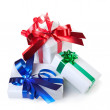 Holiday gifts with color ribbons isolated on white — Stock Photo