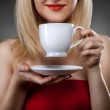 Woman in red holding cup and smiles — Stock Photo #4850447