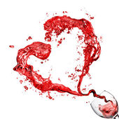 Heart from pouring red wine in glass goblet isolated on white — 图库照片