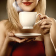 Woman in red holding cup and smiles — Stock Photo