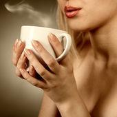 Mujer sosteniendo la taza caliente y soplar en él — Foto de Stock