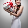 Young surprised smiling woman holding gift — Stock Photo