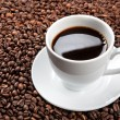 White cup with coffee beans - Photo