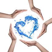 Corazón de chapoteo de agua con las manos humanas aisladas en blanco — Foto de Stock